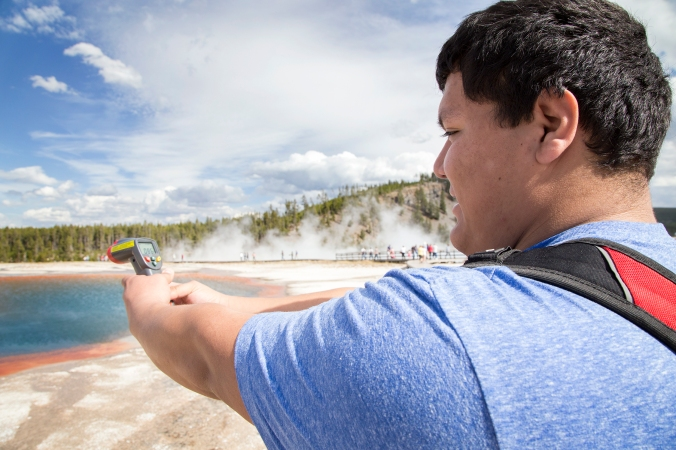 Jose Gonzalez captures the temperature of a hot spring in Yellowstone on a field trip with Professor Suki Smaglik.